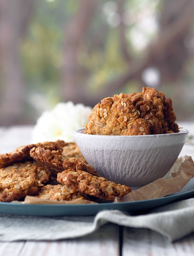 bowl and plate of Anzac biscuits sitting on a table in front of a window