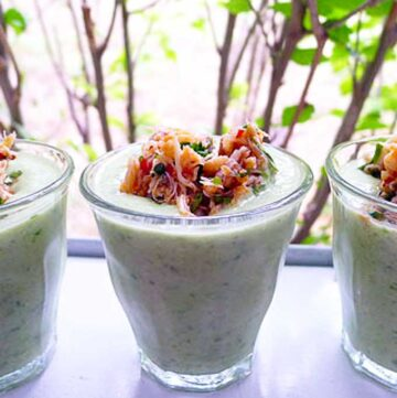 glass with chilled cucumber soup topped with spicy crab