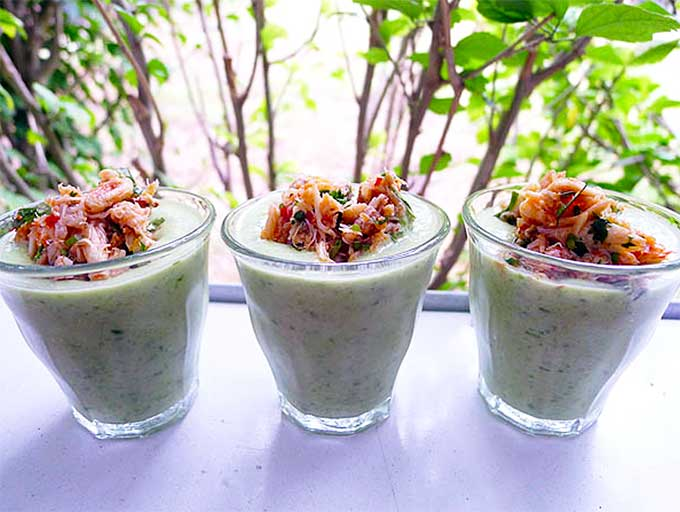 a trio of shot glasses filled with chilled cucumber soup and topped with spicy crab meat
