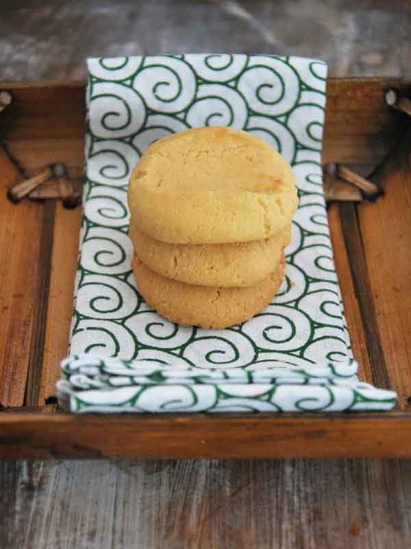 peanut butter short bread cookies sitting on green and white swirled material in a basket