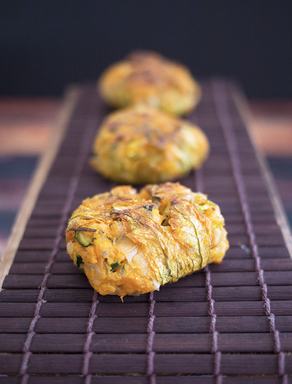 baked zucchini fritters in a row on a mat