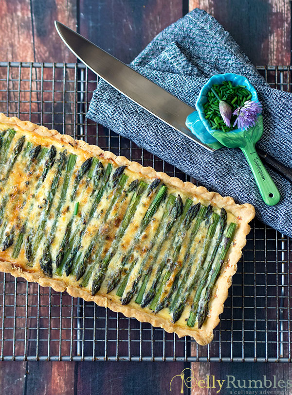 Asparagus and Pesto Tart on a cooling rack with a spoon holding chopped chives