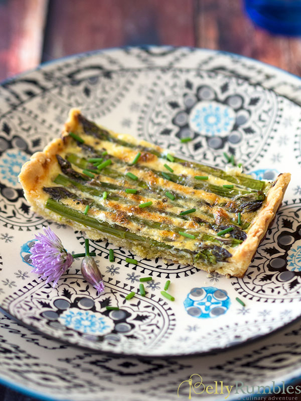 Asparagus and Pesto Tart on a patterned plate with chives and chive flowers