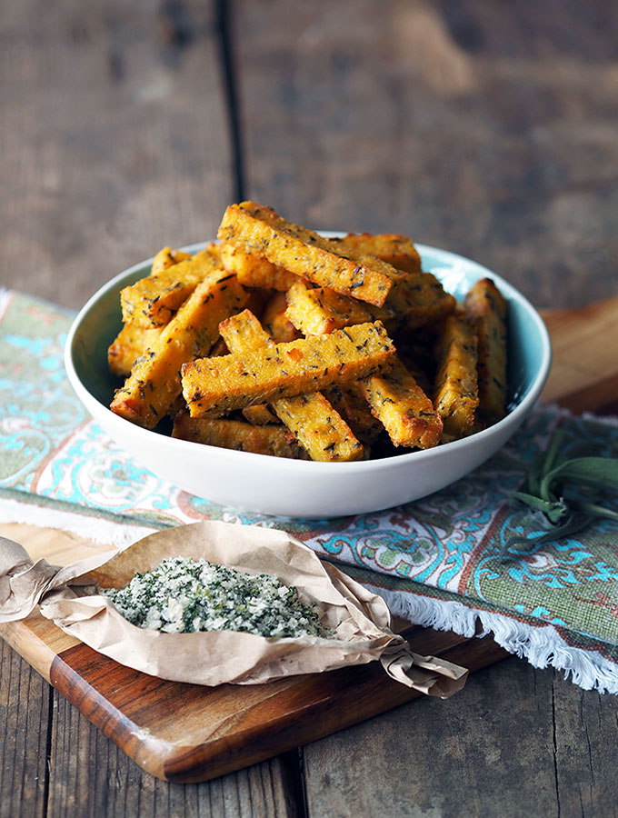 baked polenta chips in a bowl with a serving of smoked sage salt in front