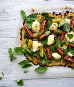zucchini pizza base recipe with fresh heirloom tomatoes, basil, pesto and mozzarella cheese