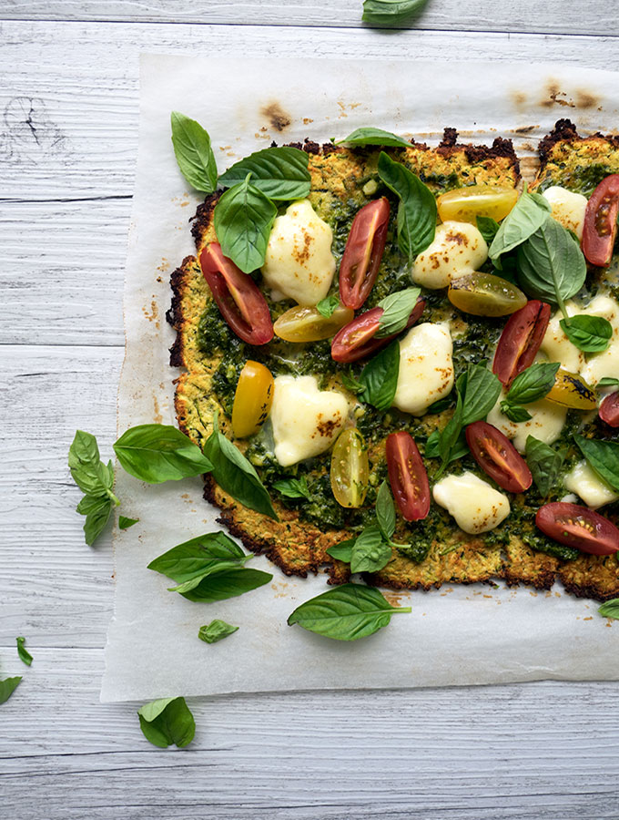 zucchini pizza base recipe with fresh heirloom tomatoes, basil, pesto and mozzarella cheese