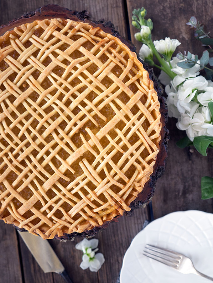 above view of lattice work on the pineapple tart with some white flowers next to the tart, and white plate and fork in bottom right hand corner
