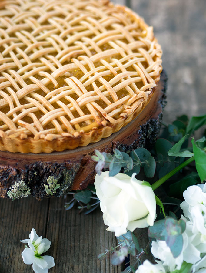 pineapple tart sitting on a round wooden board with white flowers