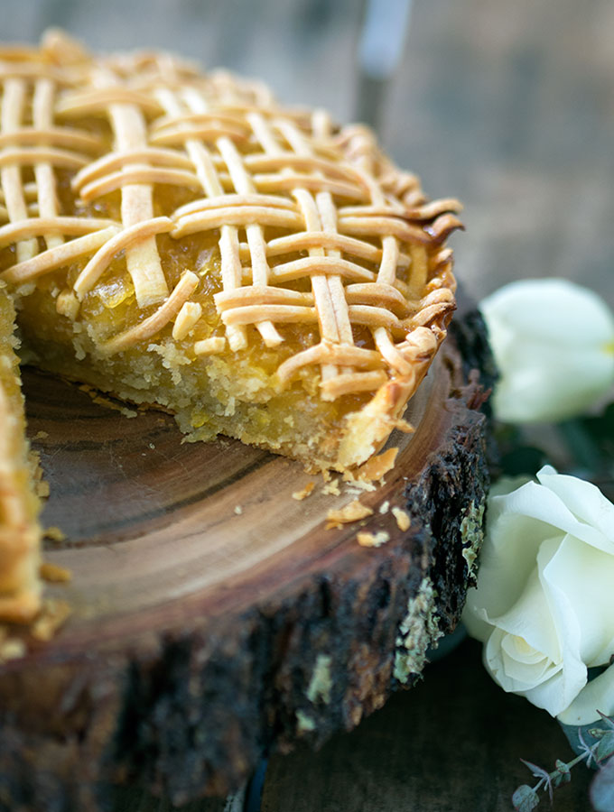 tart sitting on round wooden board with a slice removed