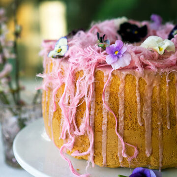 Light as air Blood Orange Chiffon Cake decorated with blood orange icing, Persian fairy floss and pretty edible flowers.