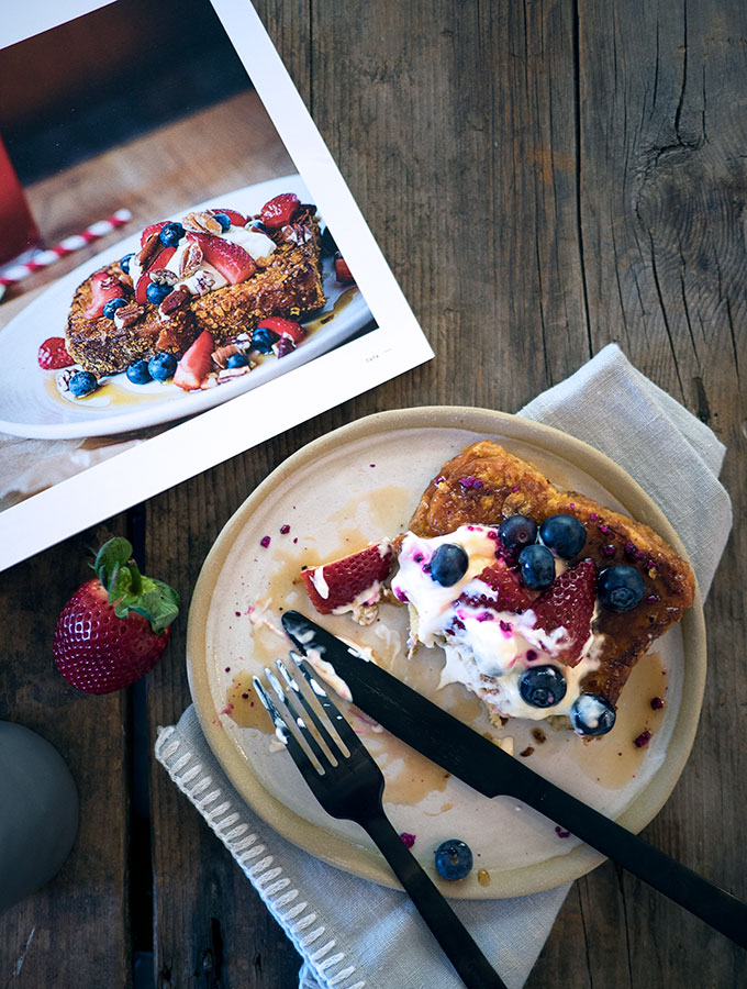 half eaten plate of french toast topped with berries and yoghurt on a stone plate on wooden table