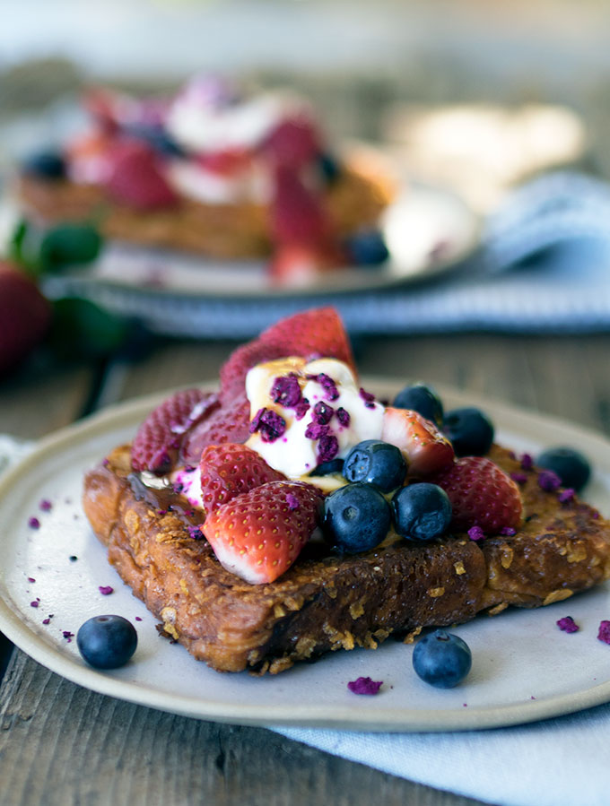 close up photo of cornflake crumbed french toast topped with strawberries and blueberries