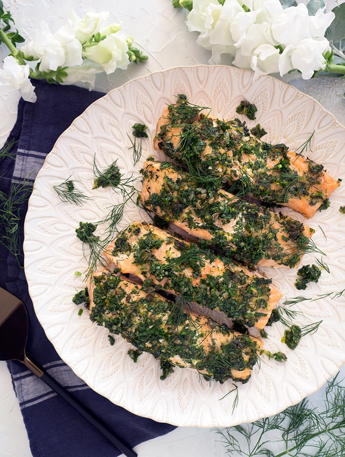 Mid week meal idea that will be on the table in 20 minutes. The capes and lemon zest add a wonderful zing to the fresh herbs used for this oven baked salmon.