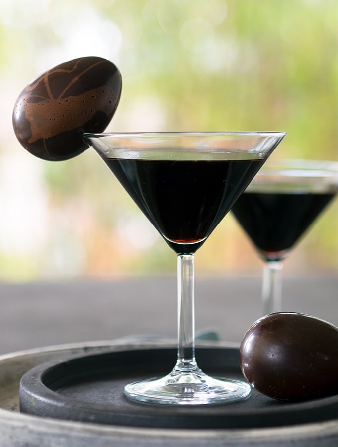 martini glass with an easter cocktail and easter egg garnish