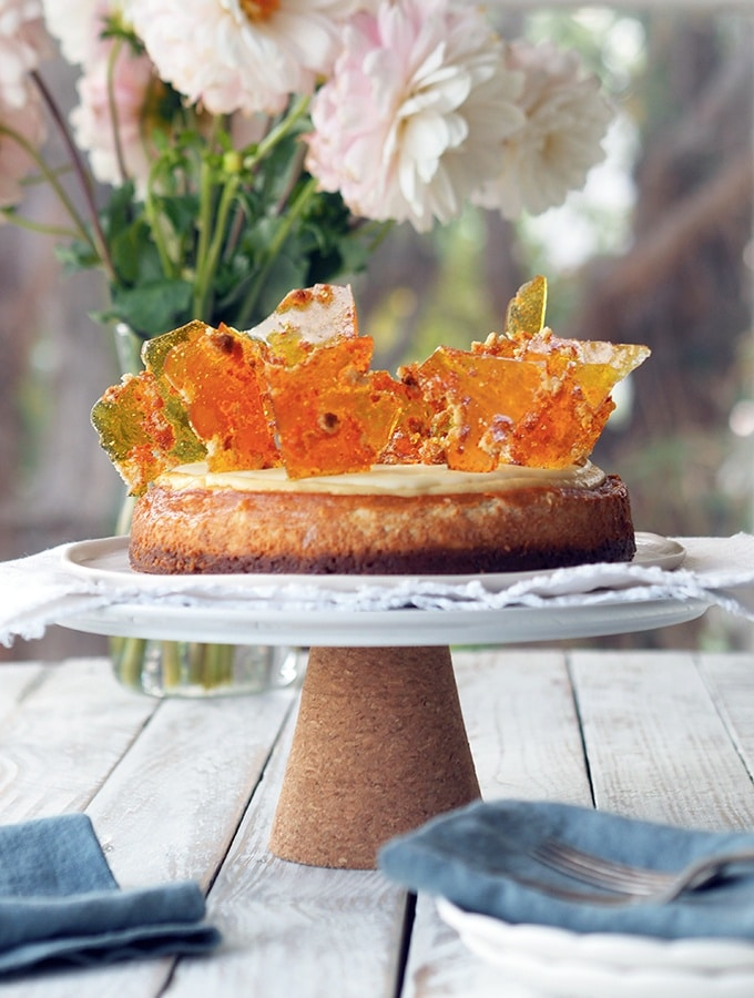 Anzac cheesecake sitting on a cake stand in front of flowers