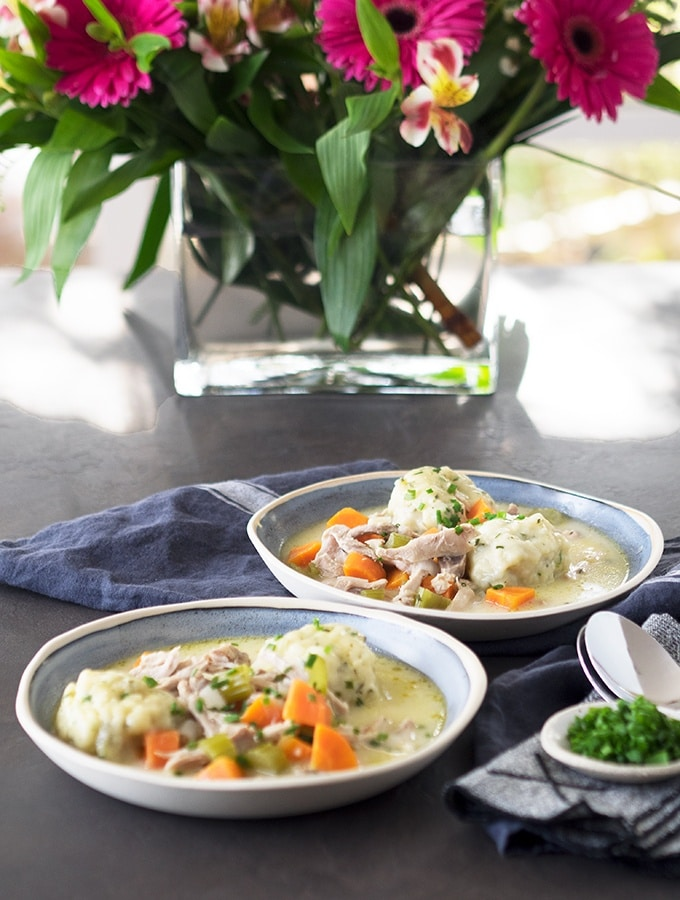 two bowls of chicken and dumplings on a table with flowers in a vase