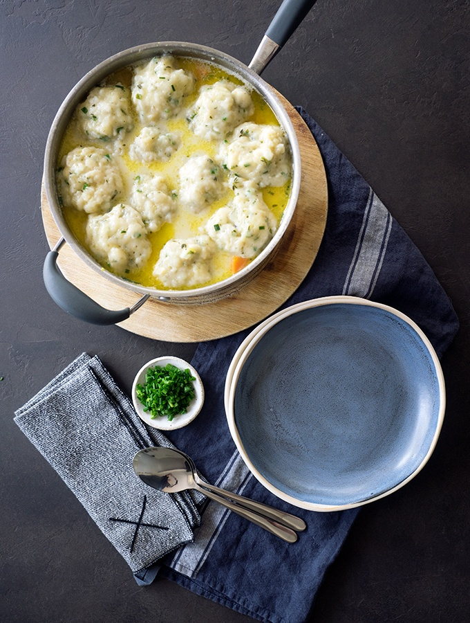above view of large pot containing cooked chicken and dumplings, bowls, spoons, napkins and chopped chives on a table