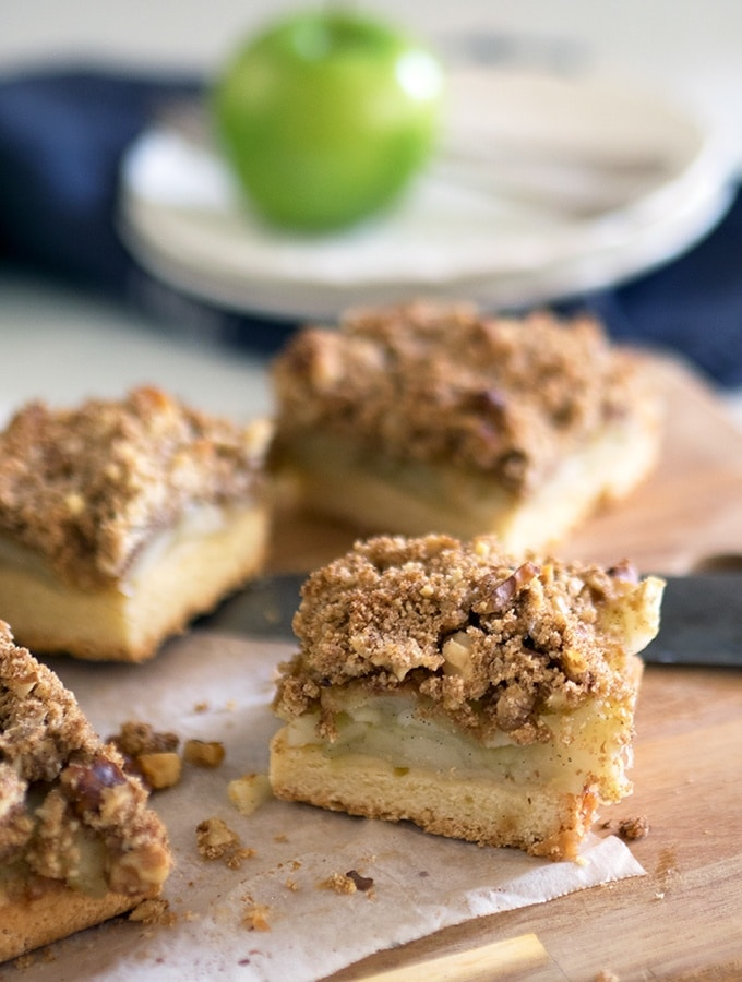 An apple slice topped with buttery walnut crumble - Apple Walnut Crumble Slice