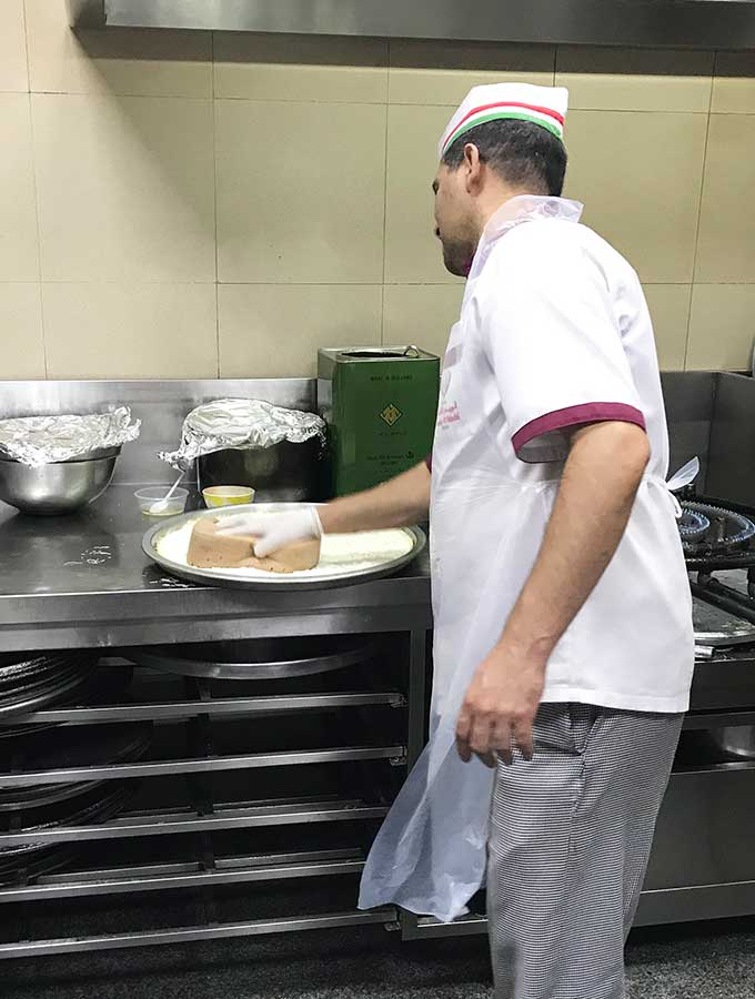 Chef sponging down base of Kanafeh