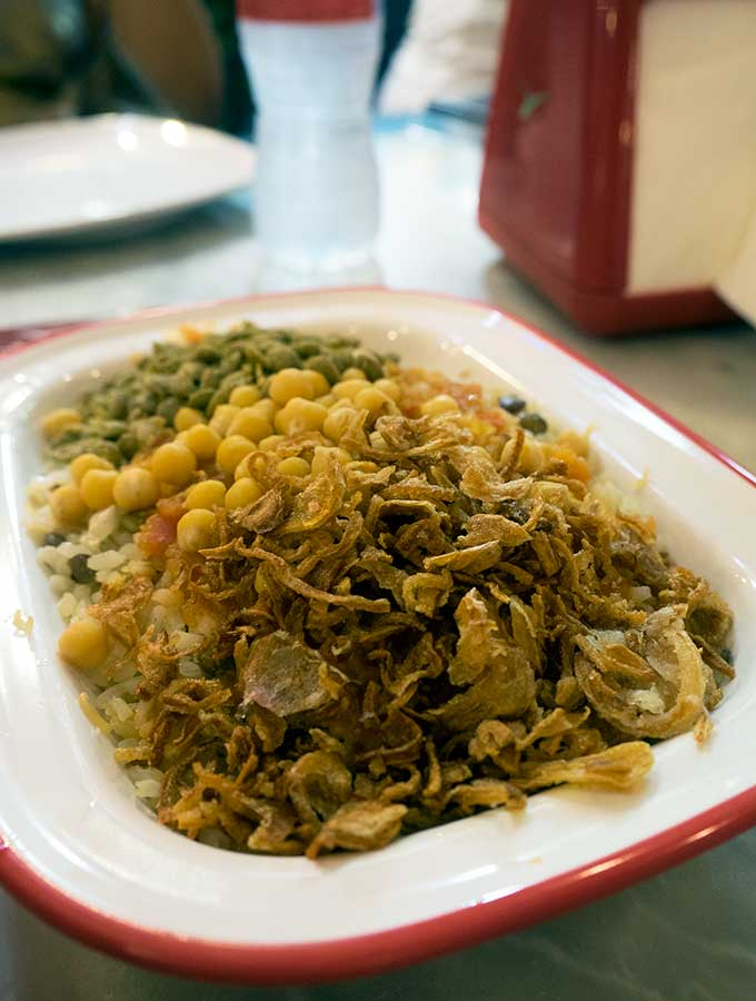Kushari with fried onions, corn and peas in Dubai