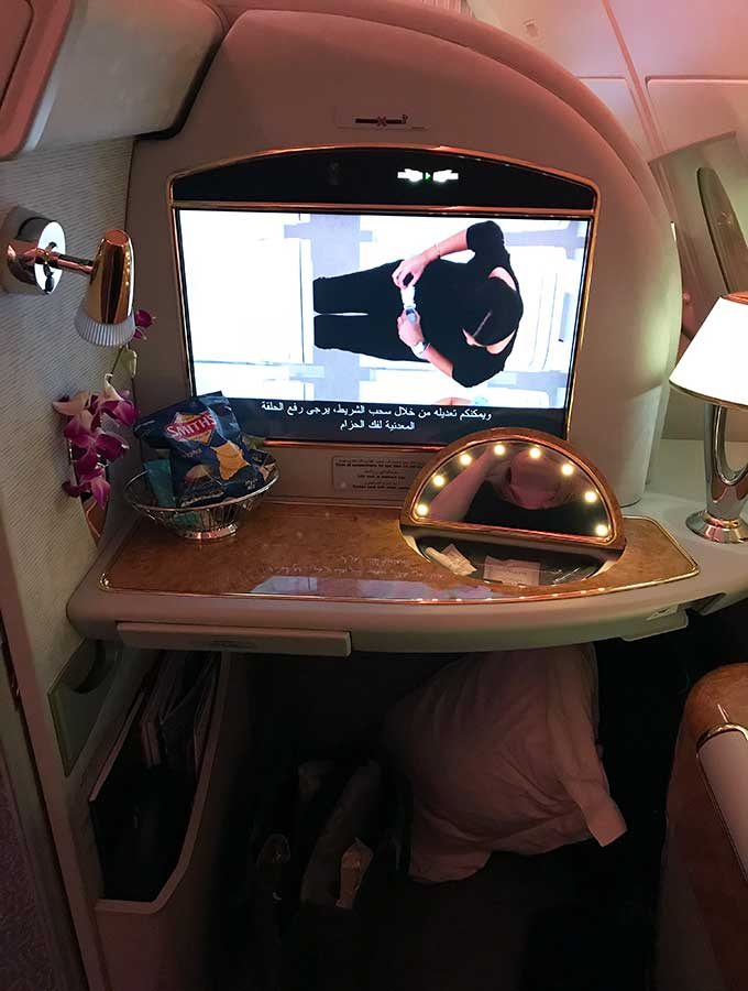 Emirates First Class Sydney to Bangkok view of entertainment unit, flowers, vanity mirror and snack basked of the first class suite
