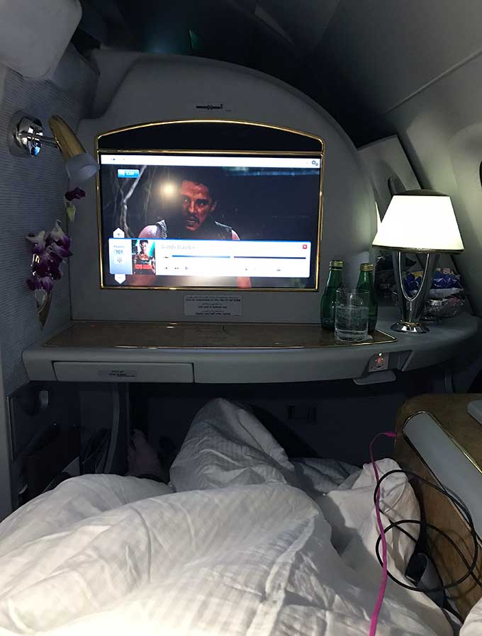 Emirates First Class Sydney to Bangkok passenger lying down in bed of the first class suite watching the entertainment unit