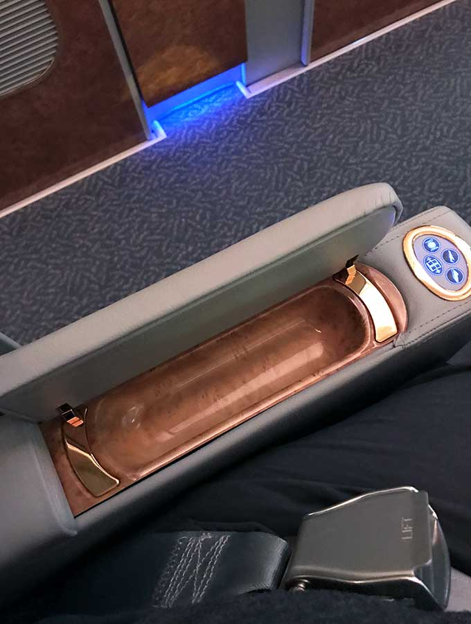 Emirates First Class Sydney to Bangkok in arm storage of the first class suite chair