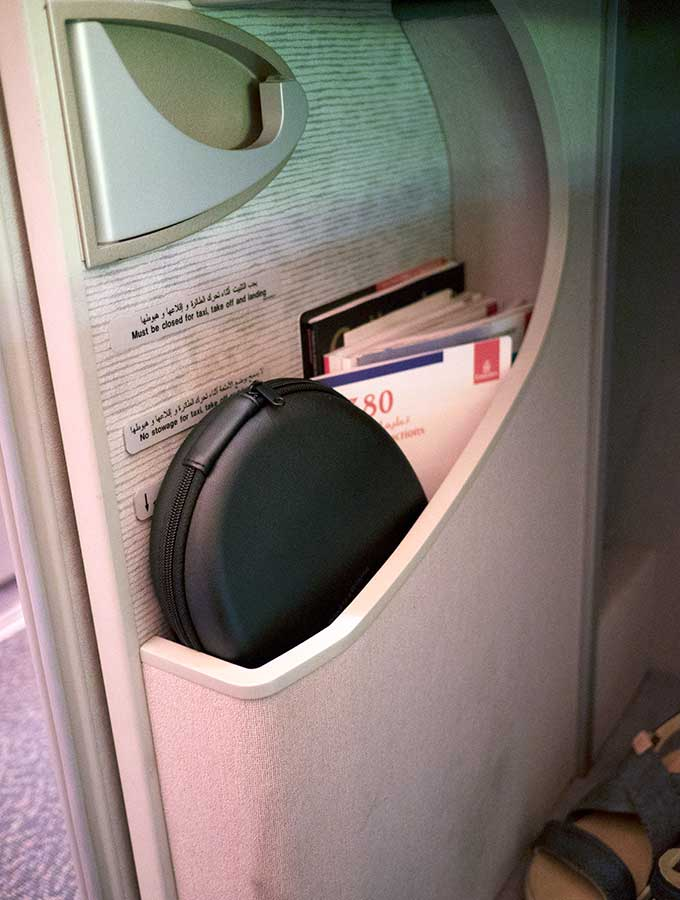 Emirates First Class Sydney to Bangkok magazine and head phone storage in first class suite