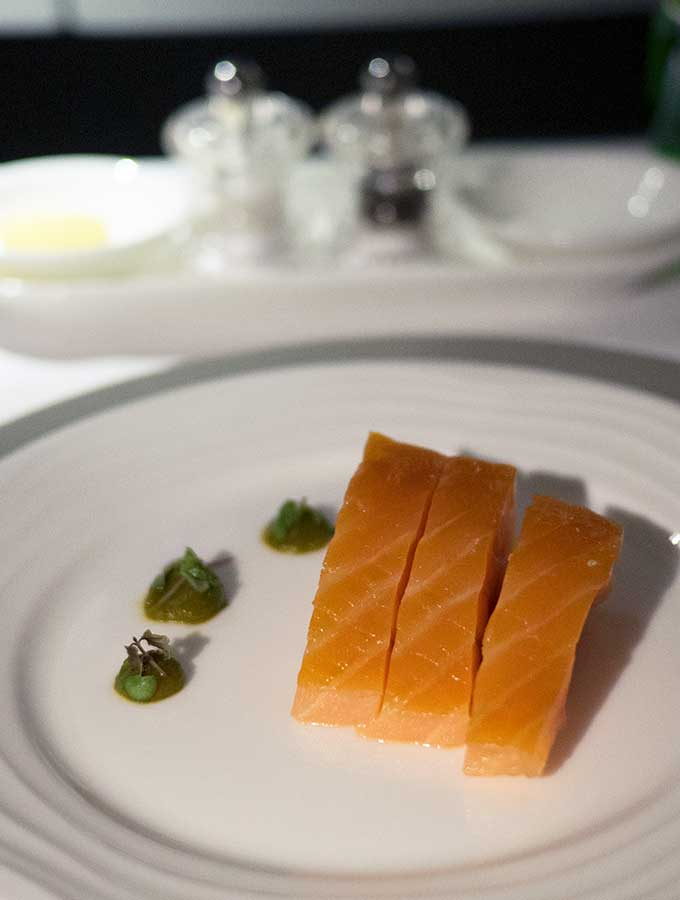 Emirates First Class Sydney to Bangkok thick slices of salmon on a plate with green sauce