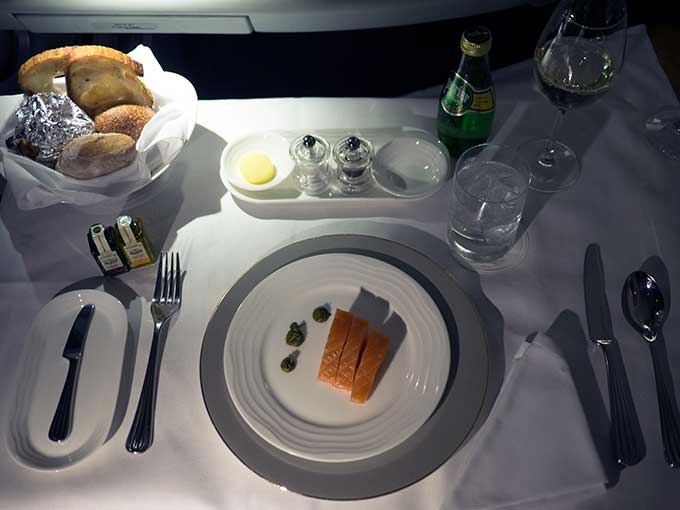 Emirates First Class Sydney to Bangkok salmon entree on plate with dots of sauce