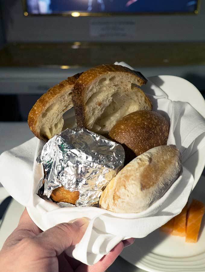 Emirates First Class Sydney to Bangkok bread basket with a variety of breads including garlic bread in foil