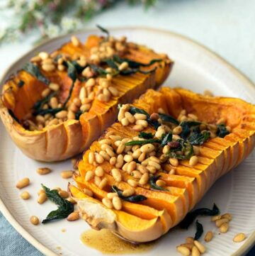 Hasselback pumpkin with browned butter pine nuts and sage on a serving plate