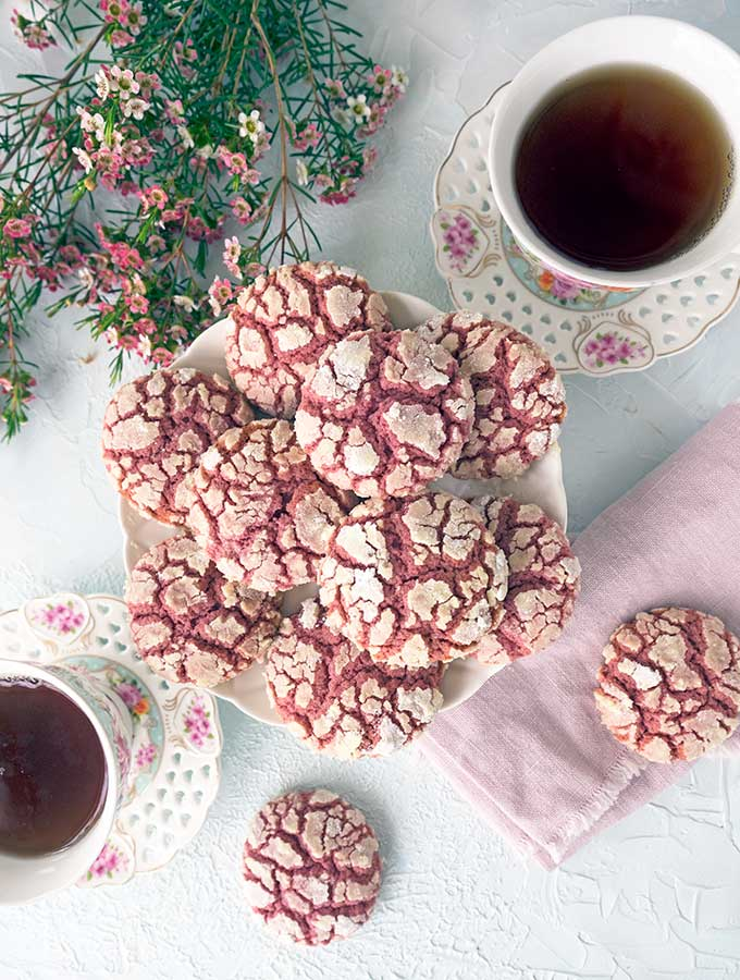 A flat lay view of Ruby Chocolate Crackle Cookies on a plate with tea cups and flowers