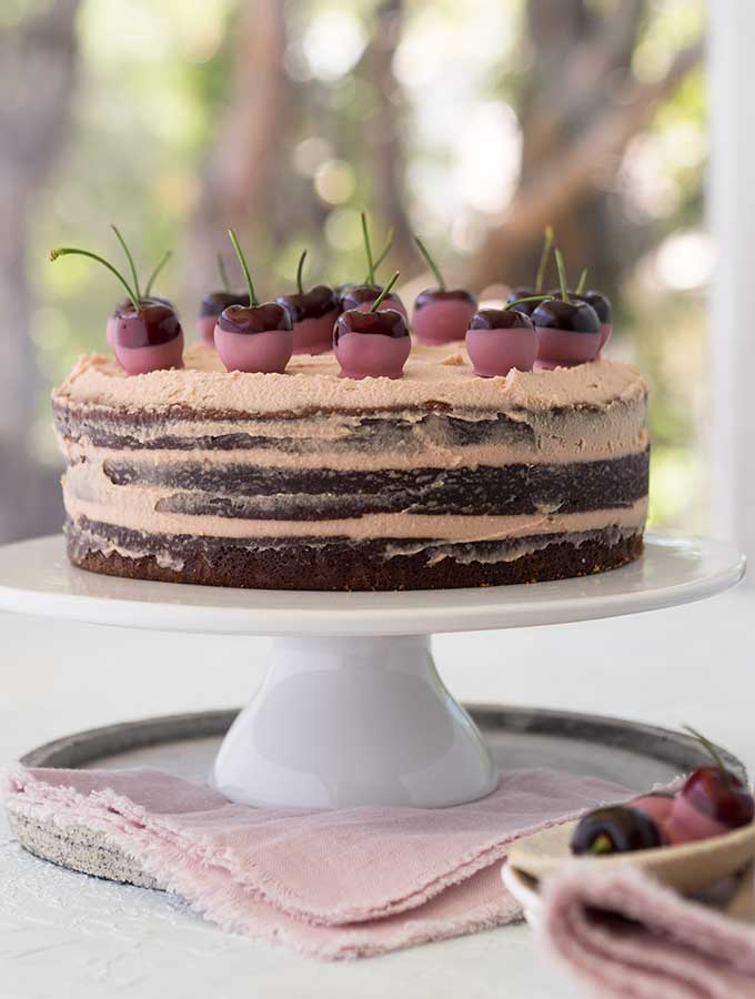 ruby chocolate mud cake on a cake stand, three layers with cherries on top