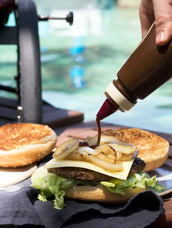 bbq sauce being squirted on an aussie burger