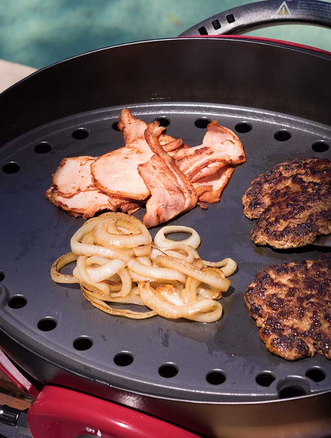 bacon onions and burger patties on the bbq