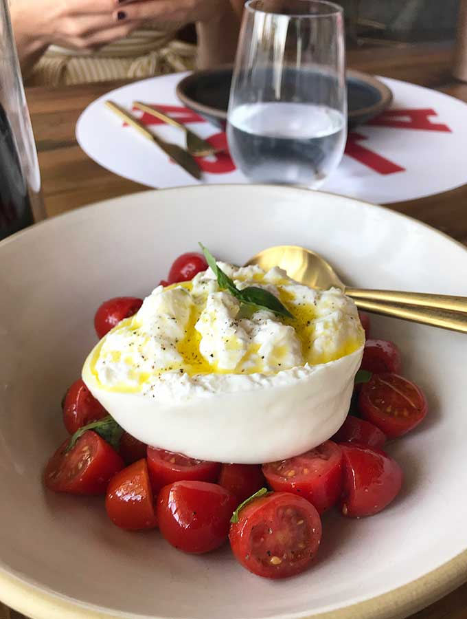 ball of burrata cheese sitting on top of ripe sliced cherry tomatoes in a white bowl