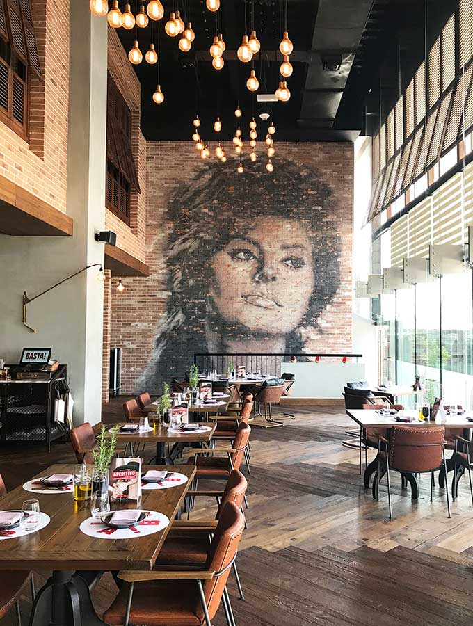 tables at Basta restaurant with a mural of sophia loren on the back wall