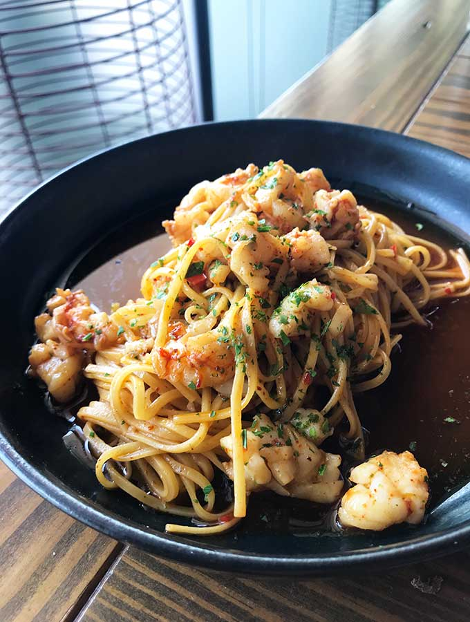 black plate with spaghetti with prawns and cream sauce