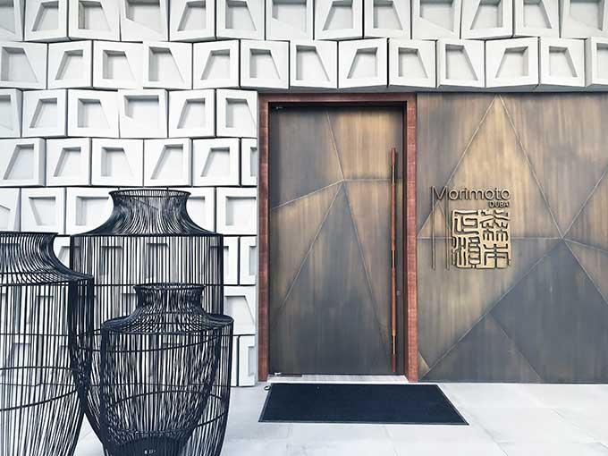 outside of Morimoto Dubai, metal doors, wicker vases and white tiles