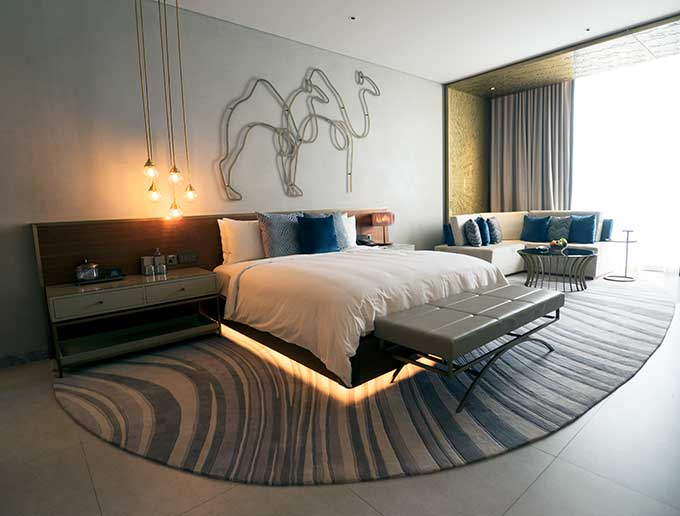 king size bed with rug underneath it. Wire sculpture of camels on the wall above the bed