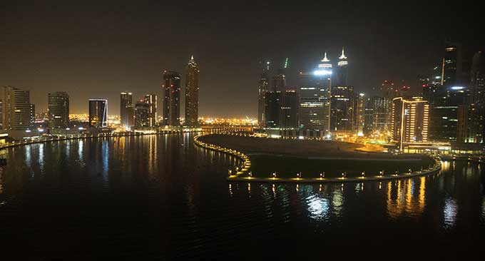 view of dubai water canal at night with buildings lit up
