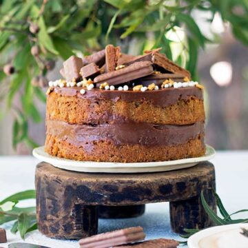 coffee sponge filled with tim tam spread on a wooden cake stand decorated with tim tams