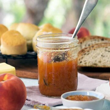 jar of peach bourbon jam with out the lid with a spoon inserted