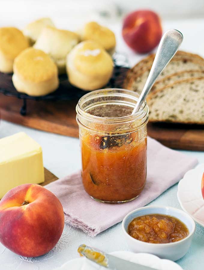 jar of peach bourbon jam on a linen serviette surrounded by scones, bread and peaches