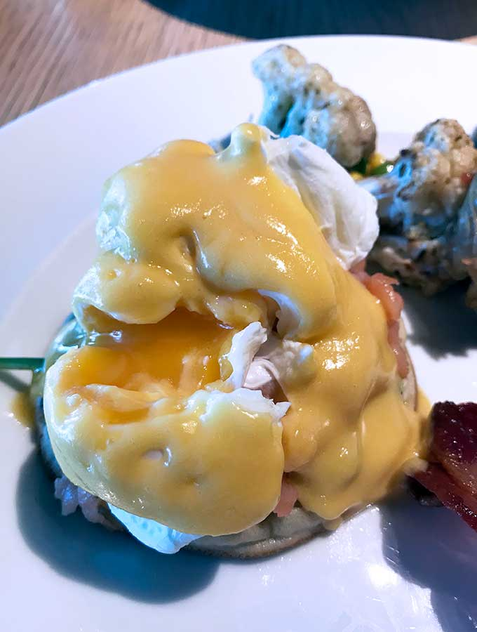 close up of eggs benedict with a runny yolk centre