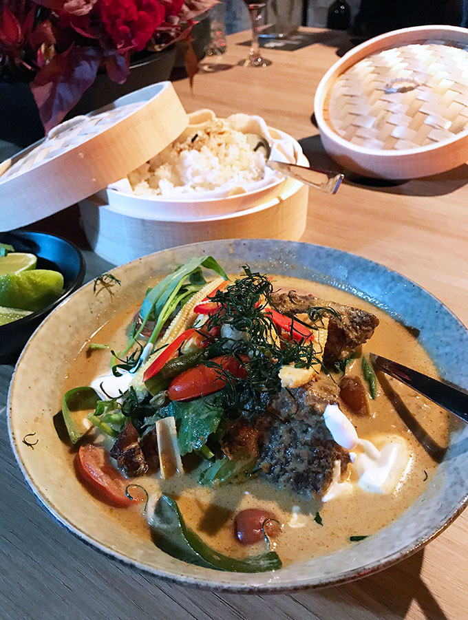 beef cheek curry in a blue bowl with rice in a basket behind