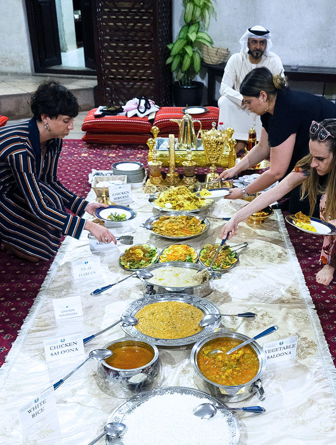 people helping themselves to various arabic dishes for iftar during ramadan