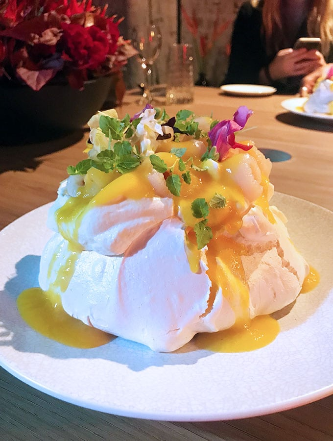 pavlova on a plate decorated with coconut cream, mango puree, lychee and flowers