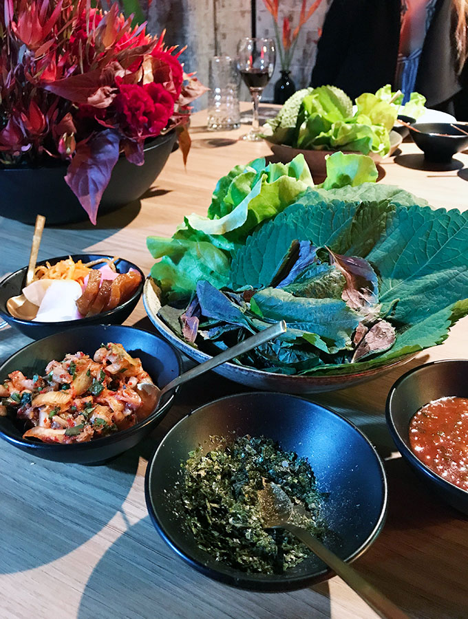 various items in bowls, pickles, chilli sauce, kimchi and dried nori. Various salad leaves in the large bowl.